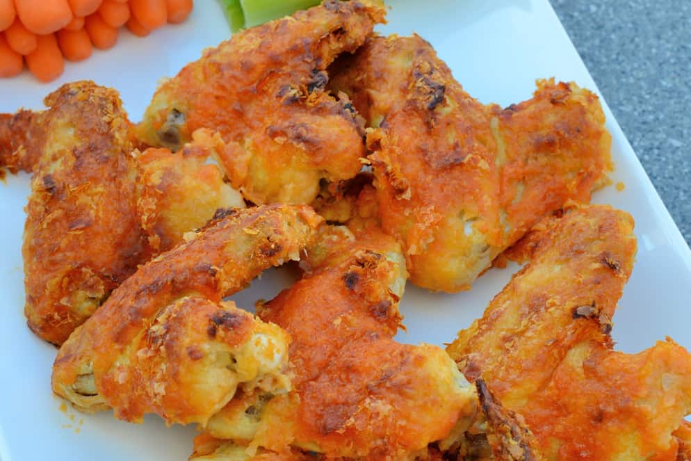"Crispy Baked Buffalo Wings uses a secret ingredient to ""bread"" wings. Bake to crispy perfection and toss in a garlic buffalo sauce. #bakedbuffalowings #crispychickenwings www.savoryexperiments.com"