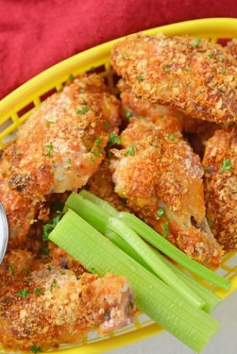 yellow basket of chicken wings with celery and dip