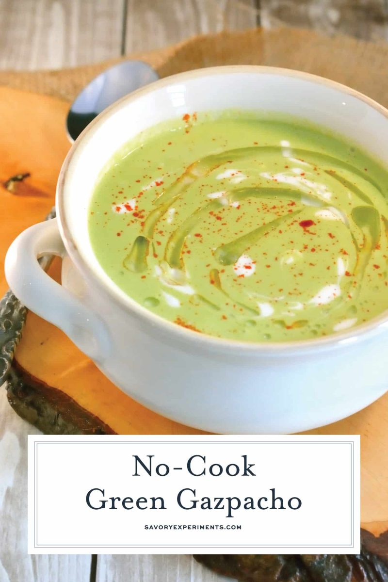 Angle of green gazpacho soup in a white bowl with garnish