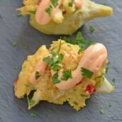 Crab Dip Stuffed Artichoke Hearts takes traditional hot crab dip and bakes in an artichoke heart, topping it with crunchy panko and Sriracha Aioli. #hotcrabdip #artichokerecipes #crabappetizers www.savoryexperiments.com
