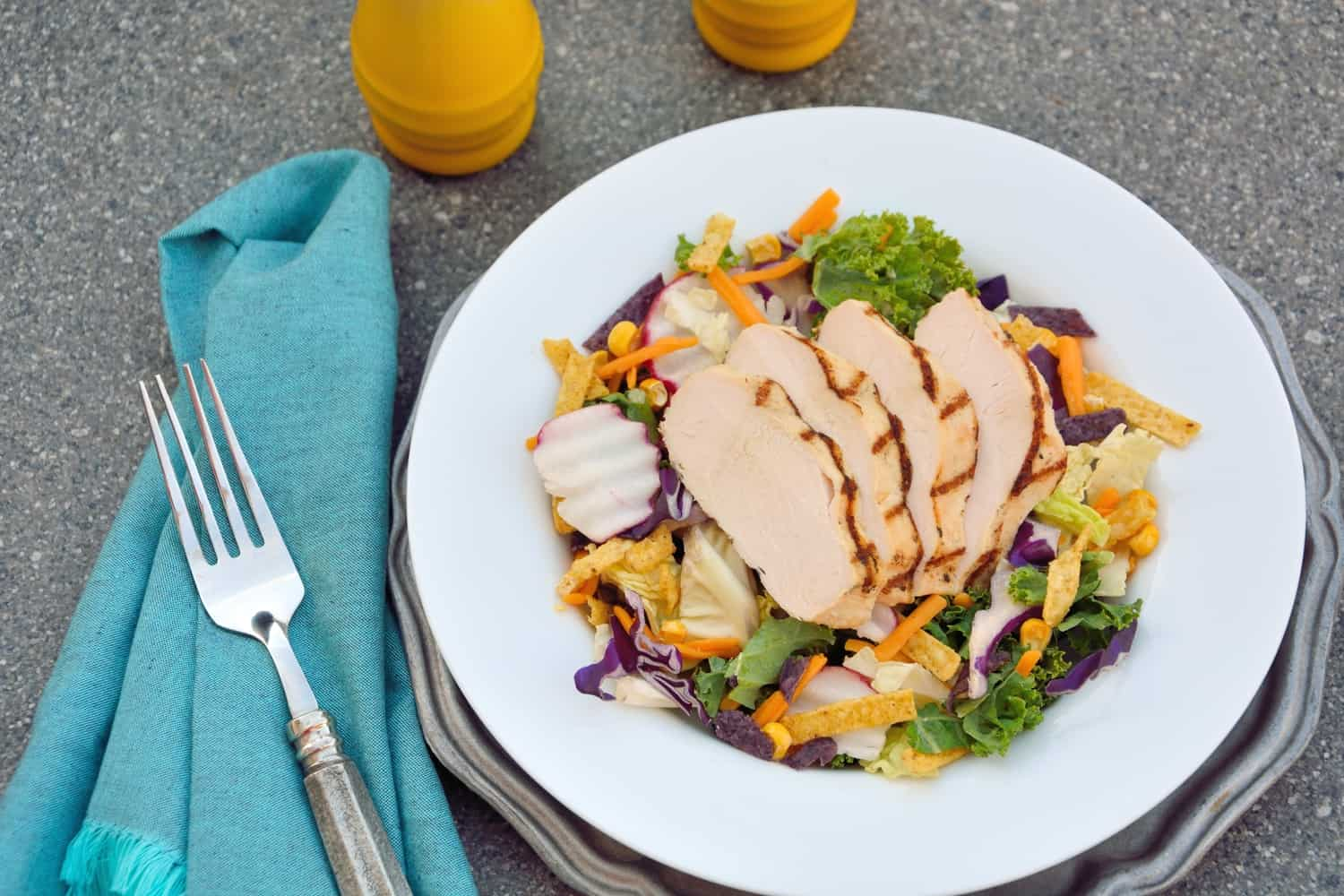 Southwest Salad with Citrus Chicken- a quick, healthy and gourmet salad with savory cabbage, red cabbage, radishes, carrots, and kale with a tangy chipotle ranch dressing and shredded cheddar cheese and crunchy tortilla strips and citrus grilled chicken.
