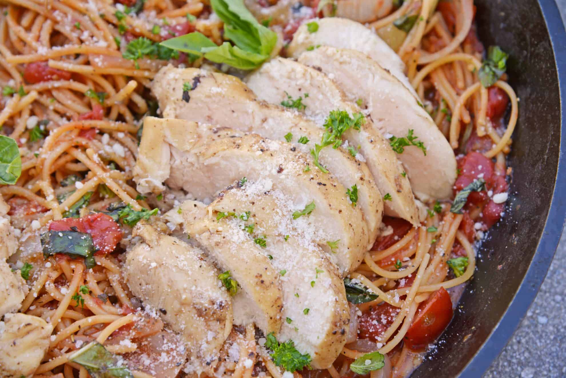 Sliced chicken in pasta with tomato and fresh basil