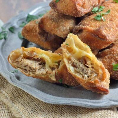 Pull Pork and Smoked Gouda Egg Rolls Recipe - Succulent, sweet and zesty pulled pork wrapped in a crispy egg roll with silky smoked gouda cheese and served alongside Avocado Green Goddess Dressing.