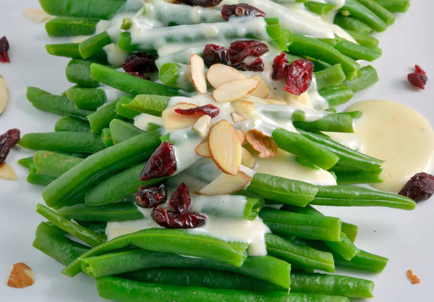 Greens Bean in a Mascarpone Cream Sauce Recipe- Steamed green beans in a rich and creamy mascaprone cream sauce topped with sweet dried cranberries and crunchy sliced almonds.