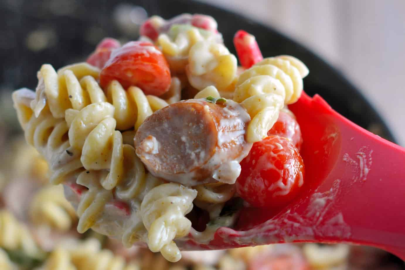 Creamy Cajun Pasta is rotini in a cream sauce with cajun seasoning, smoky andouille sausage, sautéed peppers, red onion and grape tomatoes. Takes 20 minutes to make! #cajunpasta #easypastadishes www.savoryexperiments.com