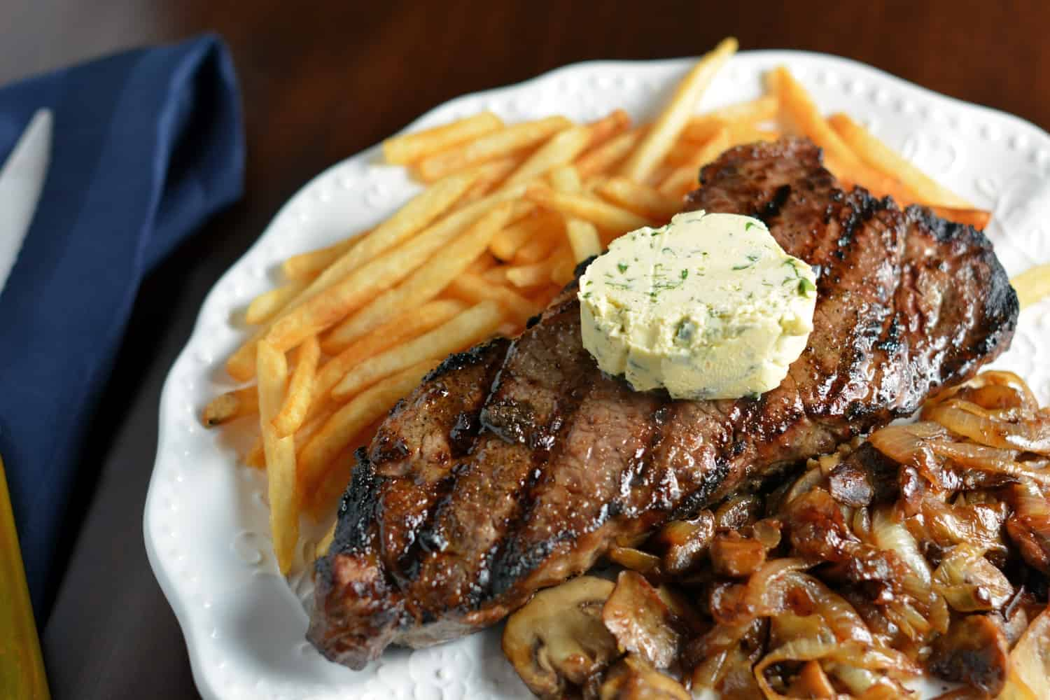 A juicy seasoned steak over crispy French fried potatoes, topped with tangy maitre d'hotel butter and served with sauteed garlic mushrooms and onions.