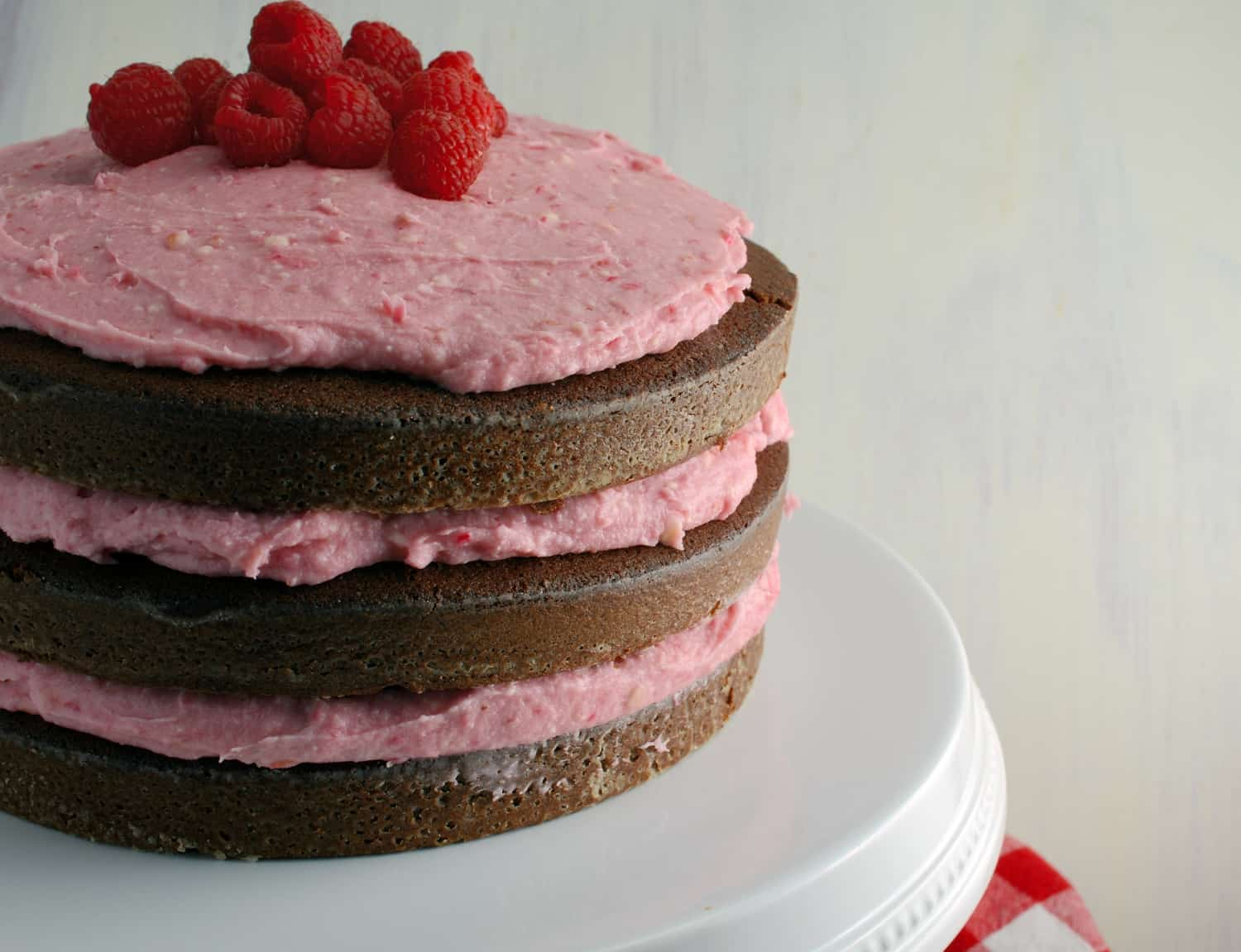 "Chocolate Cake with Raspberry Buttercream- ""naked cakes"" are all the rage and so simple! Moist, rich, and delicious dark chocolate cake that's perfect for Valentine's Day!"