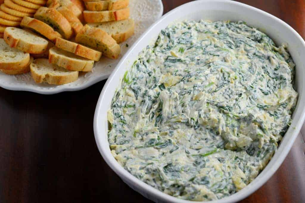 Spinach and Artichoke Dip Recipe- Serve with spinach and artichoke dip with crostinis, crackers, chips or veggies. It even tastes great on a turkey sandwich! Come see my secret ingredient for out-of-this world spinach and artichoke dip!