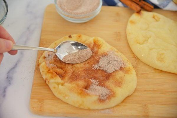 spooning cinnamon sugar onto flatbread