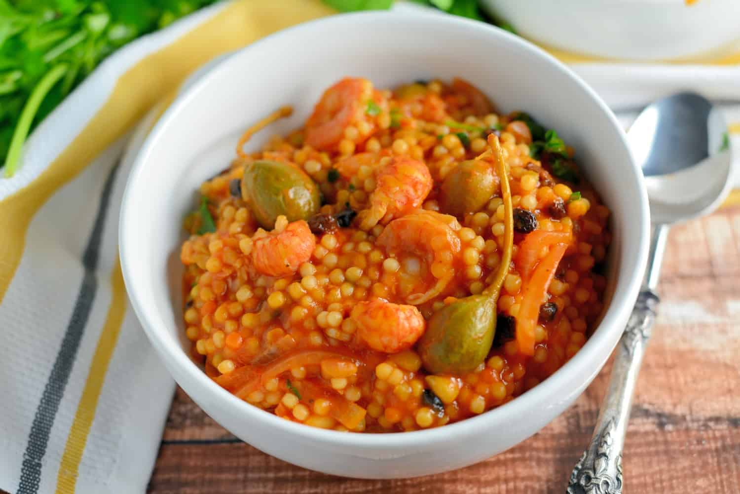 Italian Seafood Stew is a quick seafood recipe using couscous, tomatoes, currants and caper berries. This Italian stew comes together in just 20 minutes from start to finish! #italianseafoodstew #italianstew www.savoryexperiments.com