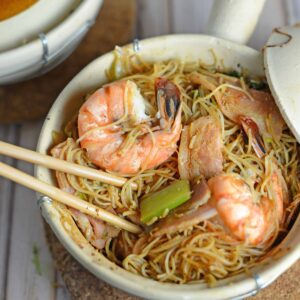 Thai Shrimp with Glass Noodles- one pot Thai dish cooked in a clay pot, cast iron or a Dutch oven. Shrimp steam between a layer of bacon and aromatics and glass noodles tossed in spy sauce. Topped with a zesty Thai sauce and fresh greens. Also known as Kung Op Wun Sen.