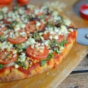 Tomato and Pesto Pizza Recipe - The BEST Homemade Pizza! This is vegetarian and super easy, using 2 types of tomatoes, pesto, mozzarella and feta cheese and toasted pine nuts. Made in a standard kitchen oven! www.savoryexperiments.com