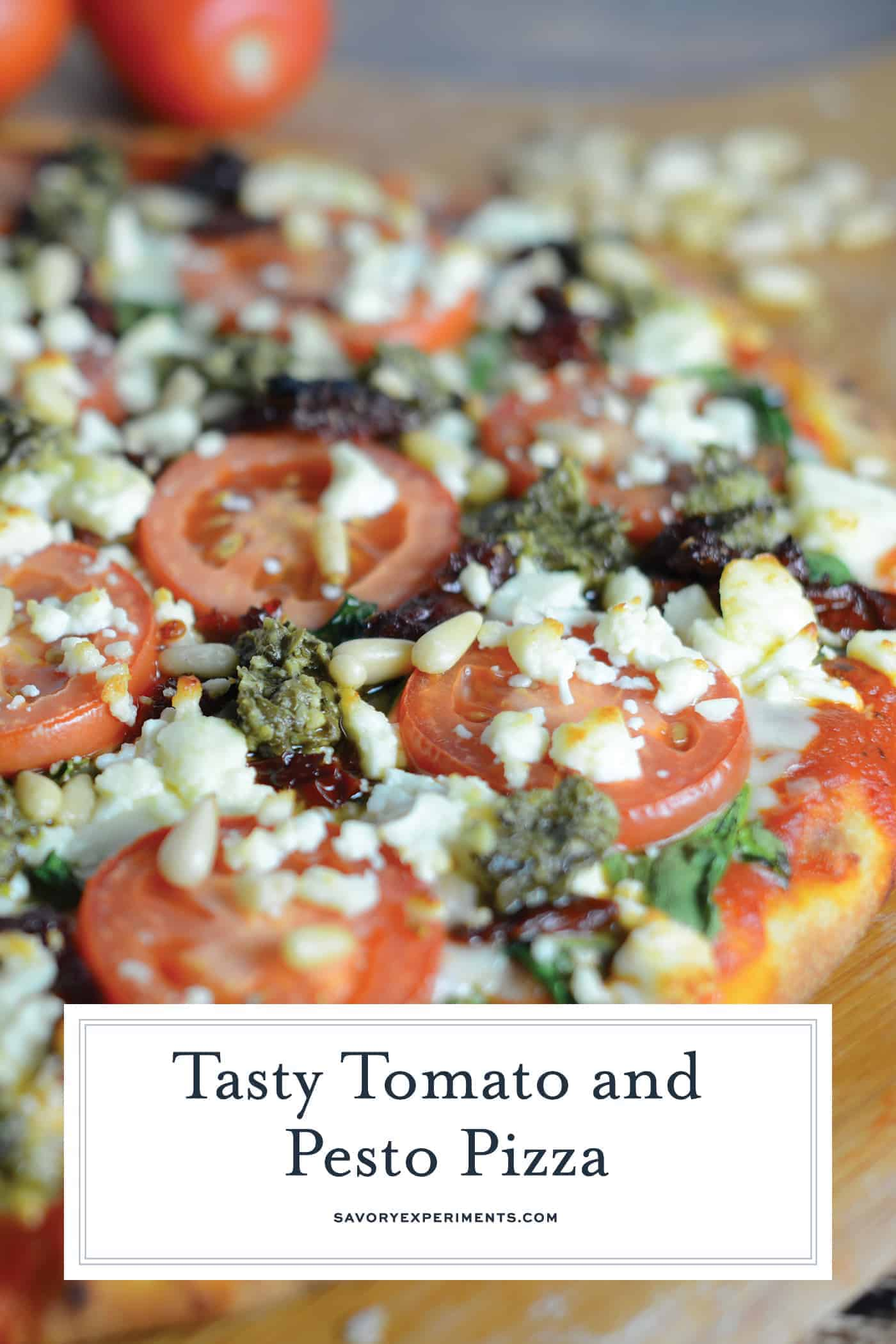 Tomato Pesto Pizza is an easy vegetarian pizza with fresh tomato slices, mozzarella and feta cheese, sun dried tomatoes, pesto and toasted pine nuts. #homemadepizza #pizzafromscratch #pestopizza www.savoryexperiments.com