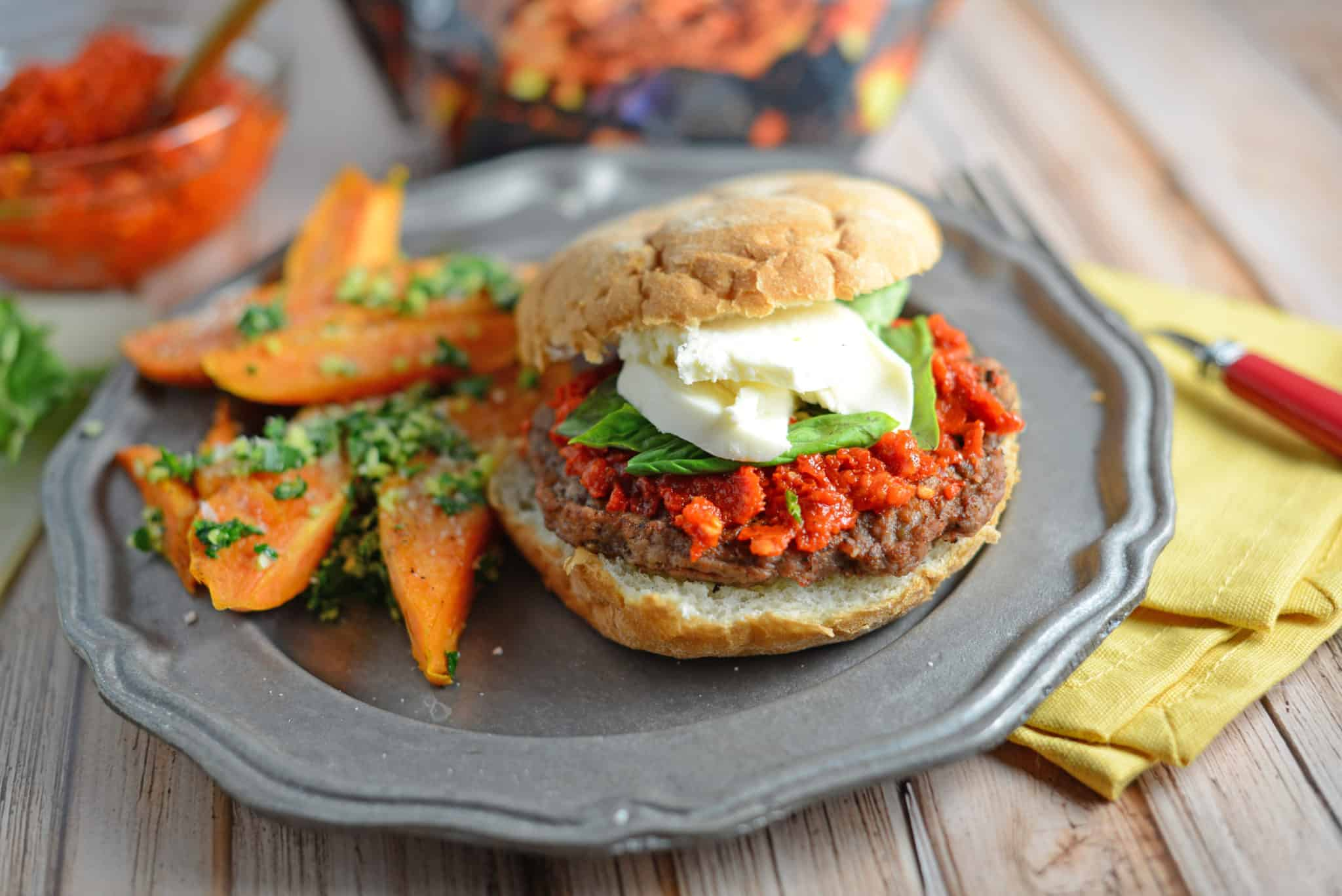 Caprese Burger Recipe - an easy sun dried tomato pesto, fresh basil and mozzarella cheese with your choice of caramelized onions and balsamic reduction. This is the best burger ever! www.savoryexperiments.com