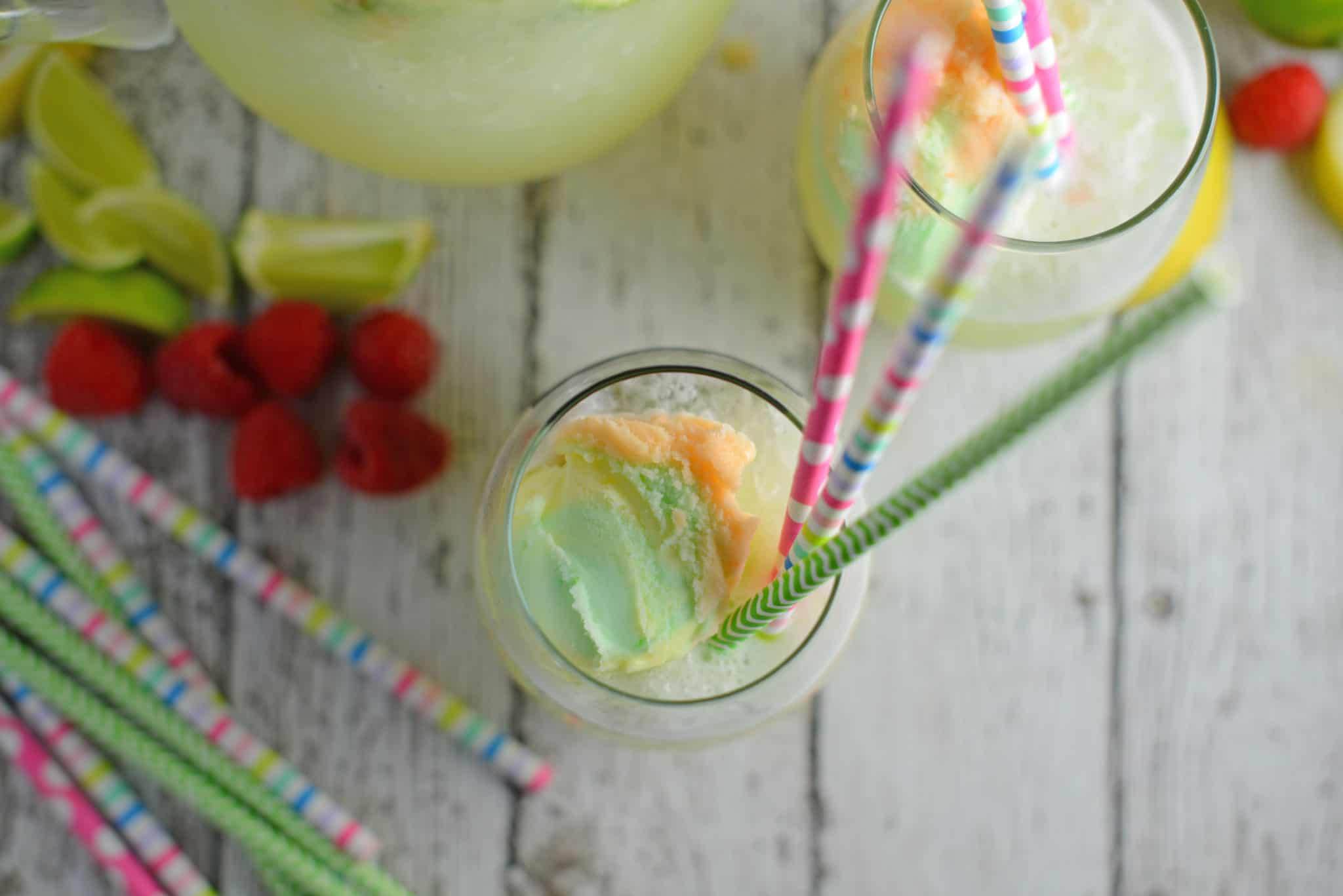 Frozen Limeade Sherbet Floats- a refreshing summer drink perfect for parties and BBQs! Cool limeade blended with ice and topped with a heaping scoop of rainbow sherbet! Perfect for kids, but an adult option available. www.savoryexperiments.com