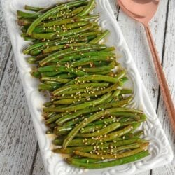 Copycat PF Chang's Spicy Green Beans topped with sesame seeds on a plate