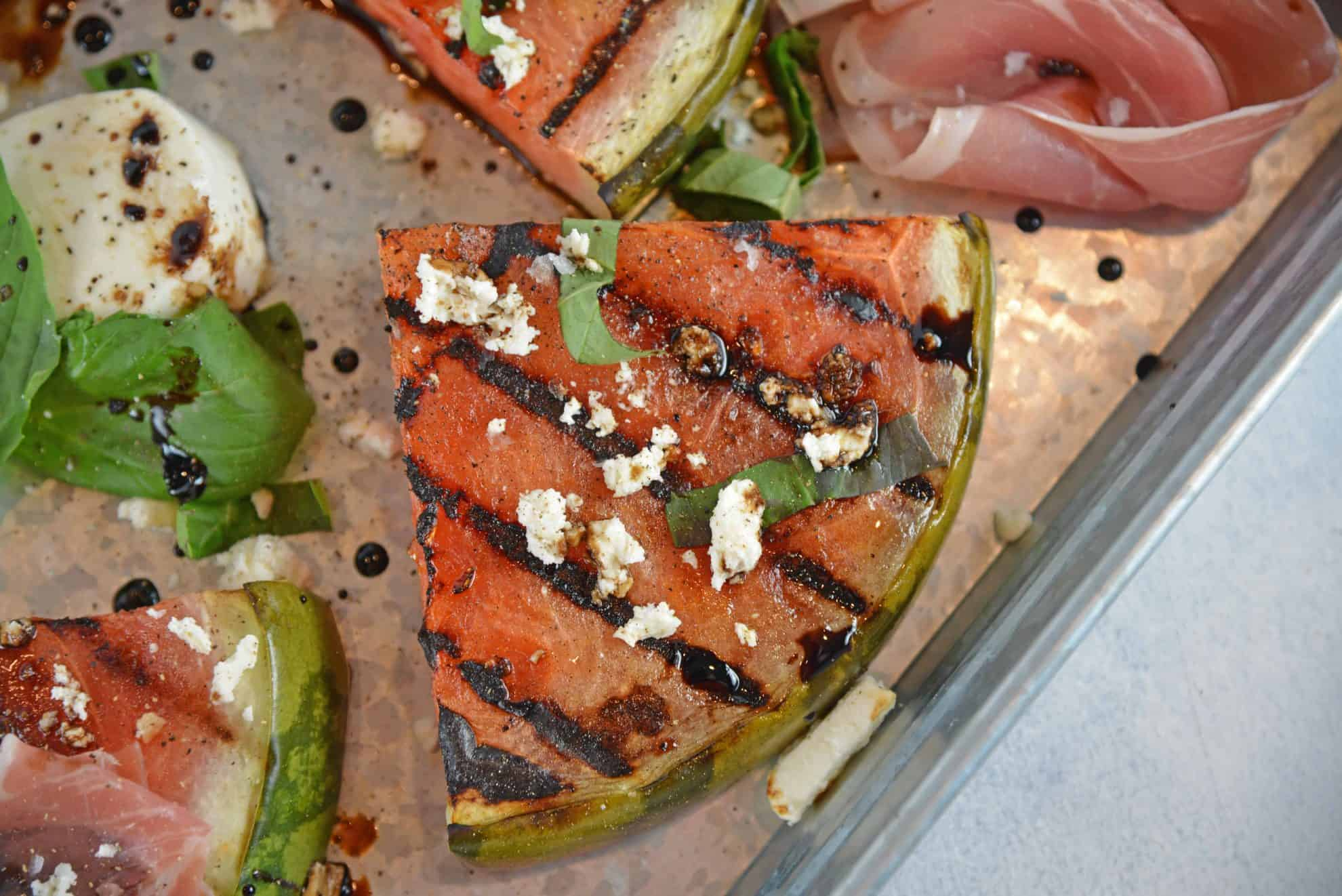 Grilled Watermelon Steaks with balsamic reduction and feta cheese are an easy BBQ side dish. Caramelized, juicy watermelon with savory cheese and sticky reduction is delicious! #grilledwatermelon #watermelonrecipes www.savoryexperiments.com