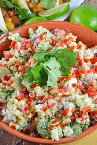 Mexican Corn Salad Recipe - Traditional Mexican street corn is turned into the best salad ever. Lime, Mexican cheese with avocado, red onions and crema mexicana. It's so good, just grab a spoon!