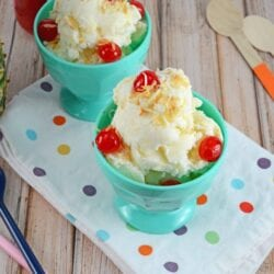 pina colada ice cream in a teal ice cream bowl with cherries