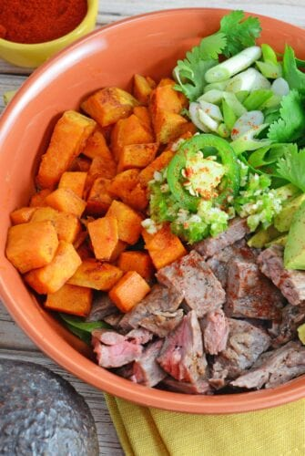 "A Beef Bowl using seasoned flank steak, spinach, baked sweet potatoes, cilantro, jalapeno, garlic and avocado, making it gluten-free and ""whole""."