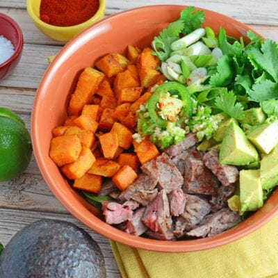 A Beef Bowl using seasoned flank steak, spinach, baked sweet potatoes, cilantro, jalapeno, garlic and avocado, making it gluten-free and