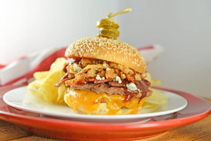 The best burger! Cowboy Burger is double patties with cheddar, blue cheese, onion strings, BBQ sauce, bacon and topped with honey habanero pickles.