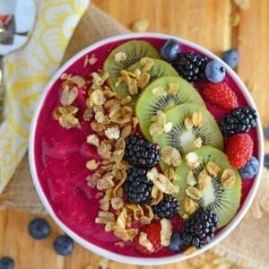 magenta smoothie bowl with fresh fruit and granola