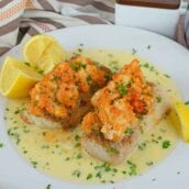 Lobster Stuffed Baked Cod is made from tender buttery cod topped with lumps of lobster meat and beurre blanc sauce! The perfect recipe for a special night! #bakedcod #stuffedcod #bakedcodrecipe www.savoryexperiments.com
