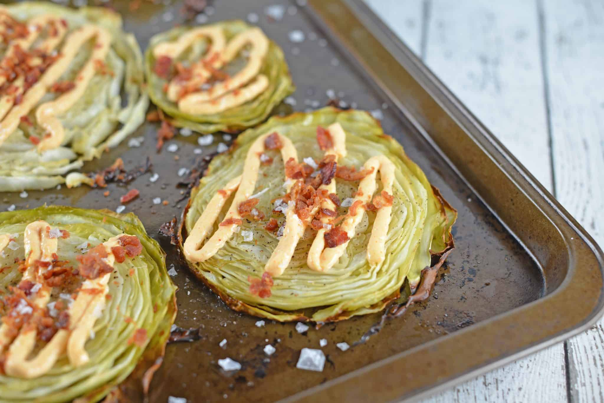 Garlic Cabbage Steaks are caramelized to perfection, then topped with a garlic and smoked paprika aioli, bacon and sea salt. Serve with any meal, especially corned beef!