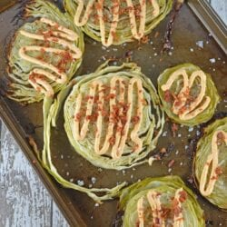 Garlic Cabbage Steaks are caramelized to perfection, then topped with a garlic and smoked paprika aioli, bacon and sea salt. Serve with any meal, especially corned beef! #cabbagerecipes #cabbagesidedish www.savoryexperiments.com