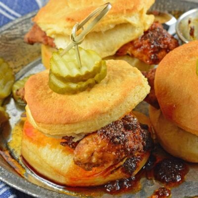 Nashville Hot Chicken Sliders are perfect as a dinner or appetizer. Crispy fried chicken dredged in spicy sauce served on buttermilk biscuits with honey habanero pickles. #nashvillehotchicken #sliderrecipes www.savoryexperiments.com