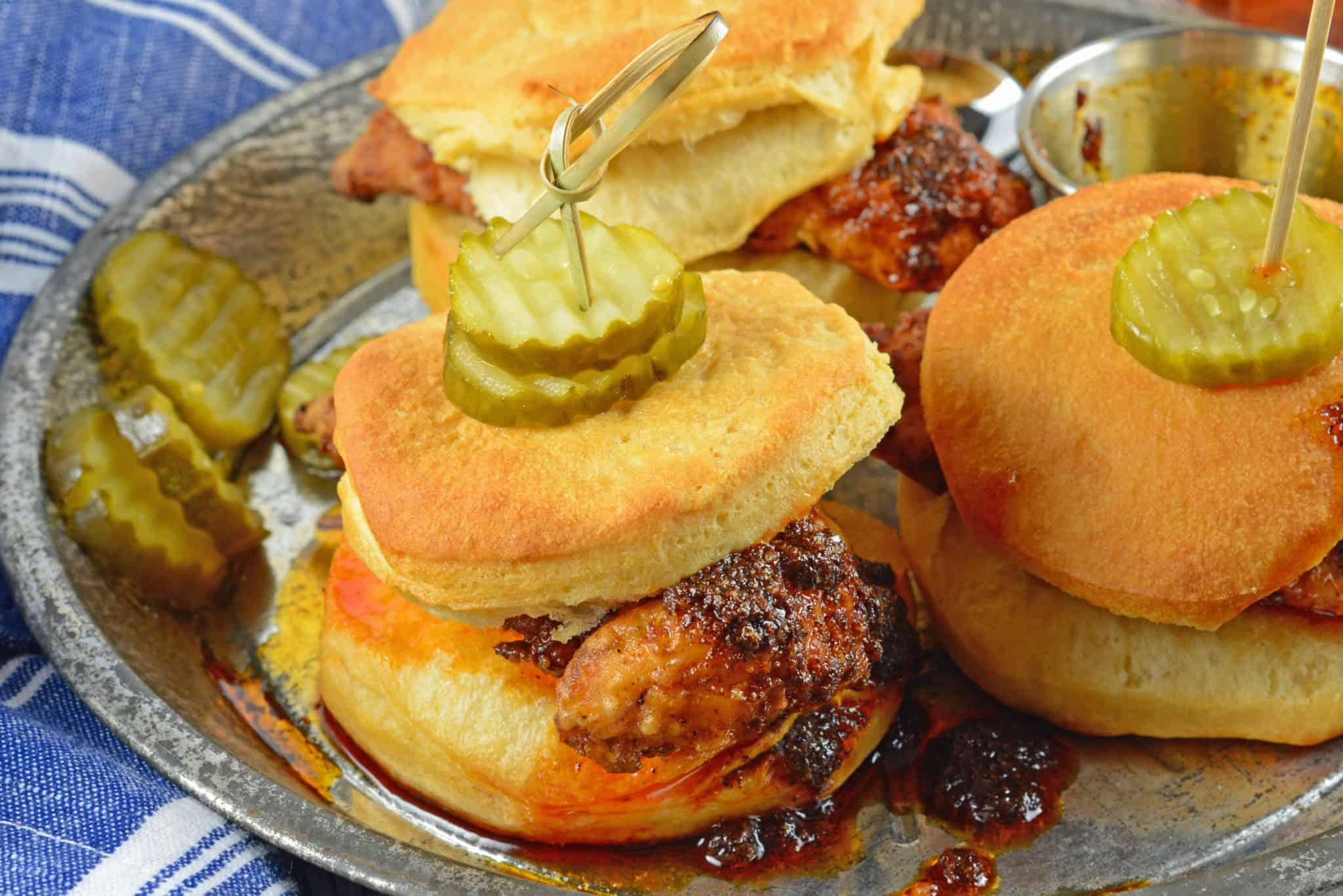 Nashville Hot Chicken Sliders are perfect as a dinner or appetizer. Crispy fried chicken dredged in spicy sauce served on buttermilk biscuits with pickles. #nashvillehotchicken #sliderrecipes www.savoryexperiments.com