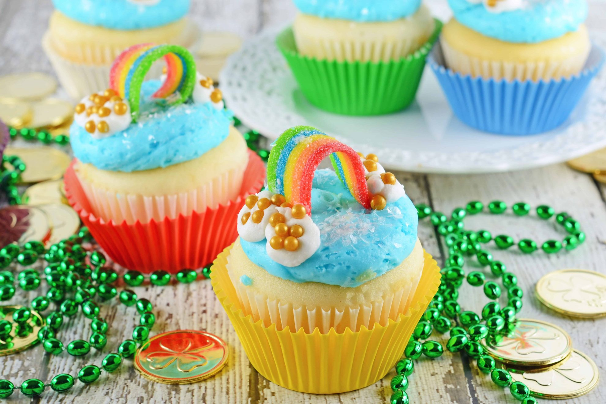 Rainbow Cupcakes are super easy and cute. The perfect cupcake for St. Patrick's Day, children's birthday parties or any random day of the week! #rainbowcupcakes #stapatricksdaydesserts www.savoryexperiments.com
