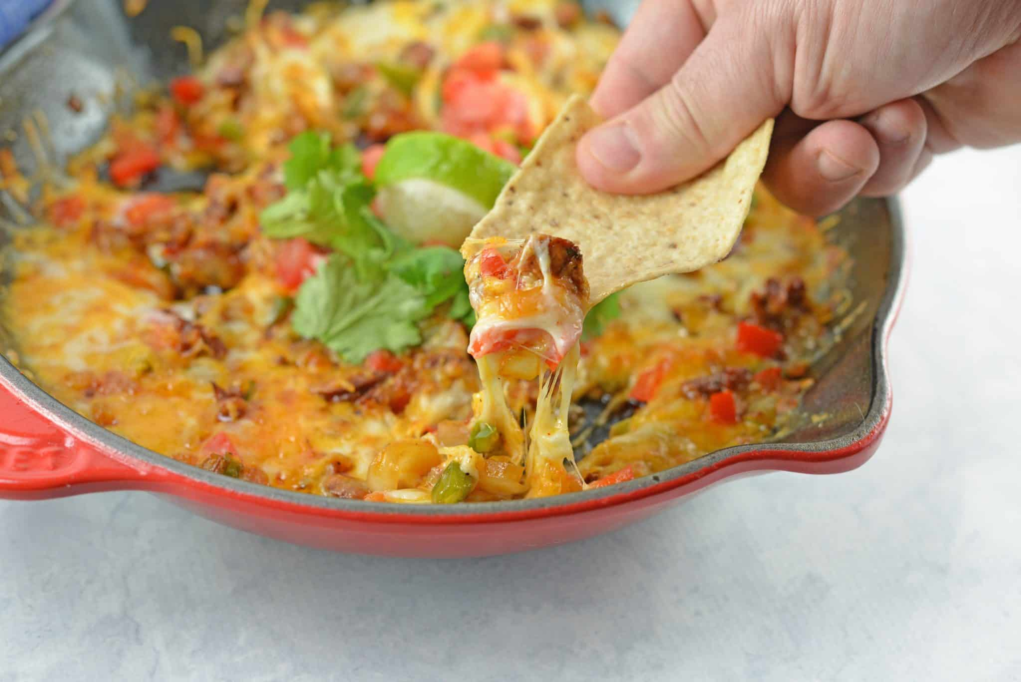 Queso Fundido with Chorizo is the best Mexican Cheese Dip made with a blend of Mexican cheeses, smoky, spicy Chorizo and fresh vegetables. #quesofundido #cheesedip www.savoryexperiments.com