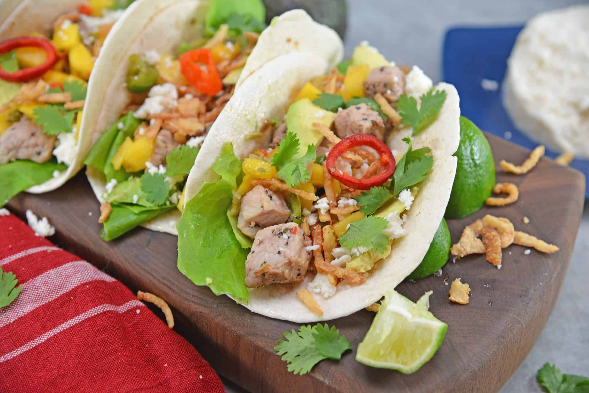 Crispy Pork Tacos are soft tacos filled with mango salsa, cool avocado, crumbly queso fresco, butter lettuce and crispy onion straws.
