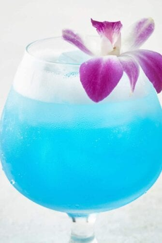 Sparkling Blue Hawaiian Cocktail topped with an orchid