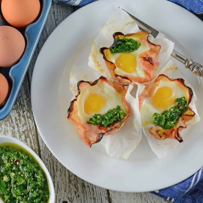 Chimichurri Egg Muffins are eggs baked in ham with a zesty chimichurri sauce made with fresh herbs and garlic. The perfect make ahead breakfast idea! #greeneggsandham #eggmuffins www.savoryexperiments.com