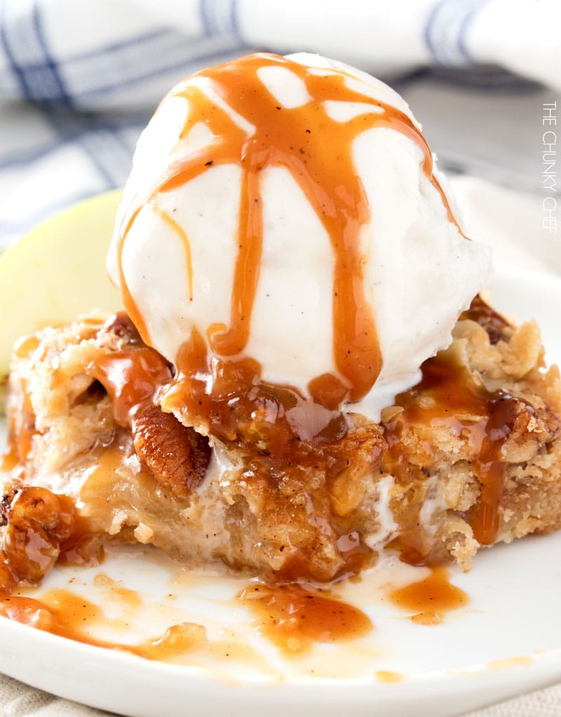 Close up of caramel apple pie bar topped with scoop of vanilla ice cream