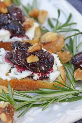 Balsamic Cherry Crostini are an easy appetizer using goat cheese and a tangy cherry balsamic reduction. The perfect holiday appetizer recipe! #crostinirecipes #goatcheeserecipes #easyappetizerrecipes www.savoryexperiments.com