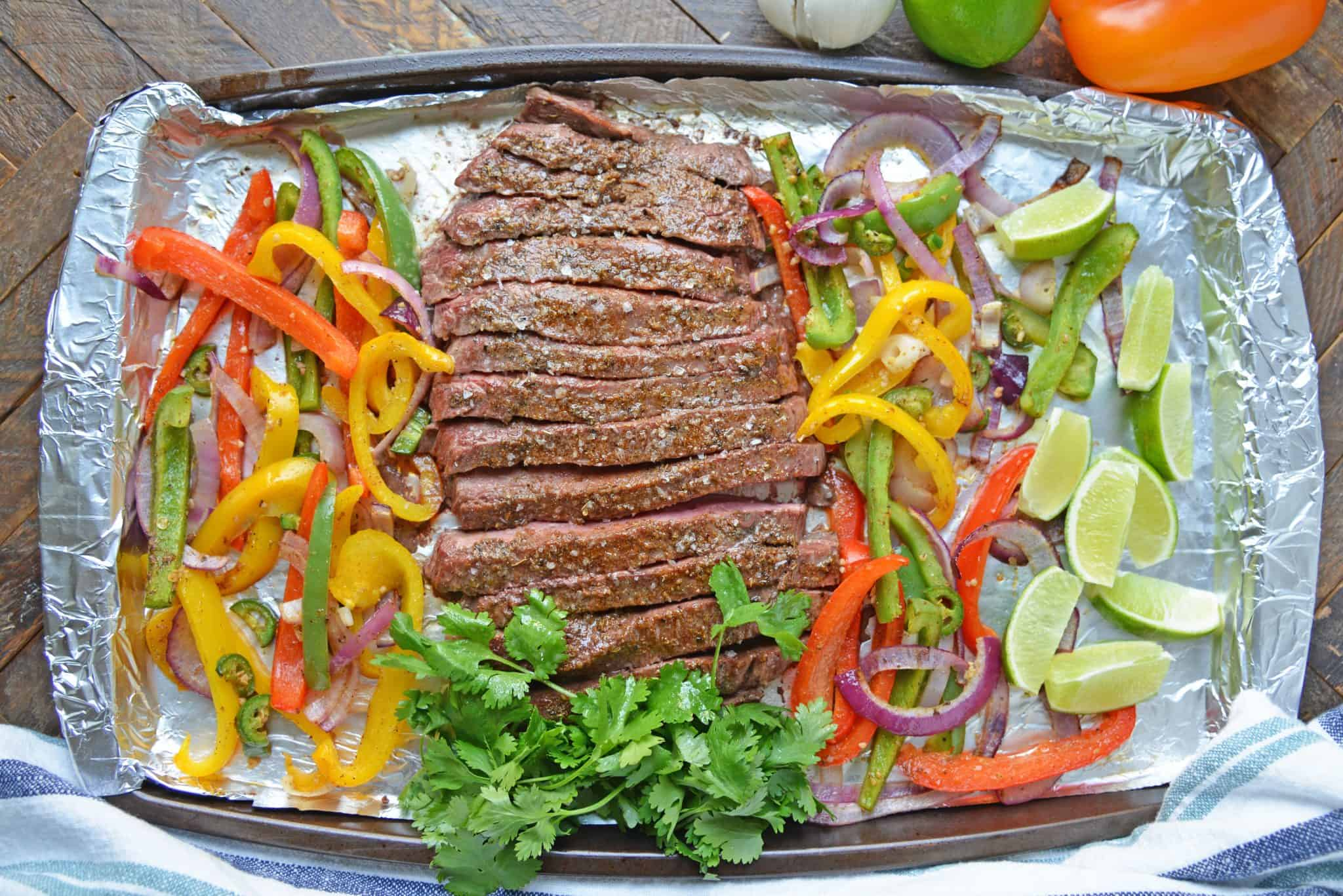 Sheet Pan Steak Fajitas are an easy weeknight meal using tender beef, homemade fajita seasoning, peppers, onions and jalapenos! #sheetpanrecipes #steakfajitas #bestangusbeef #steakholder www.savoryexperiments.com
