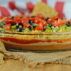 Easy party appetizers don't get much easier than this 7 layer dip! It takes chips and dip to a whole new level with refried beans, guacamole and sour cream! #7layerdip #beandip #sevenlayerdip www.savoryexperiments.com