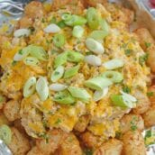 Crabby Totchos are crispy fried tater tots smothered in hot crab dip and topped with melty cheddar cheese. The perfect party appetizer! #tatertots #easyappetizerrecipes www.savoryexperiments.com