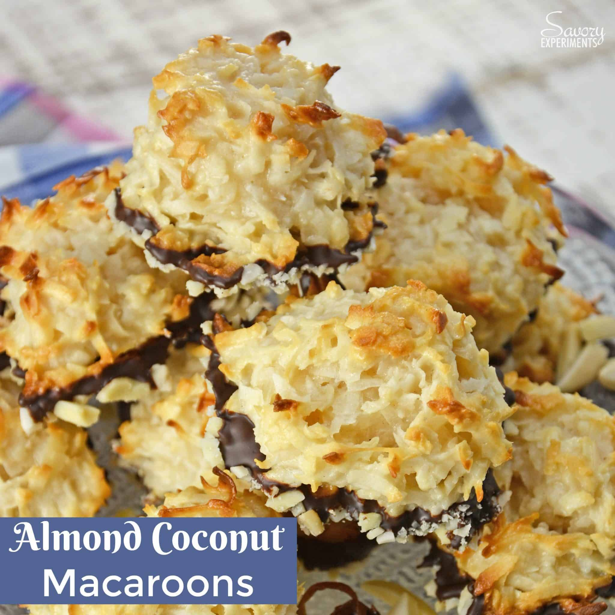 Almond Coconut Macaroons are light, fluffy coconut biscuits dipped in chocolate and almonds. Perfect as a dessert, for tea for as a an afternoon snack. #coconutmacaroons #macaroonsrecipe www.savoryexperiments.com