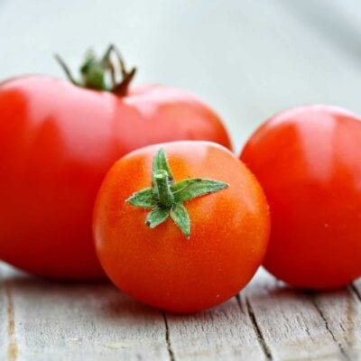 Learn how to peel a tomato in just a minute! Super easy without cooking the tomato. Perfect for sauces, salads and salsas!#howtopeelatomato #tomatoes www.savoryexperiments.com