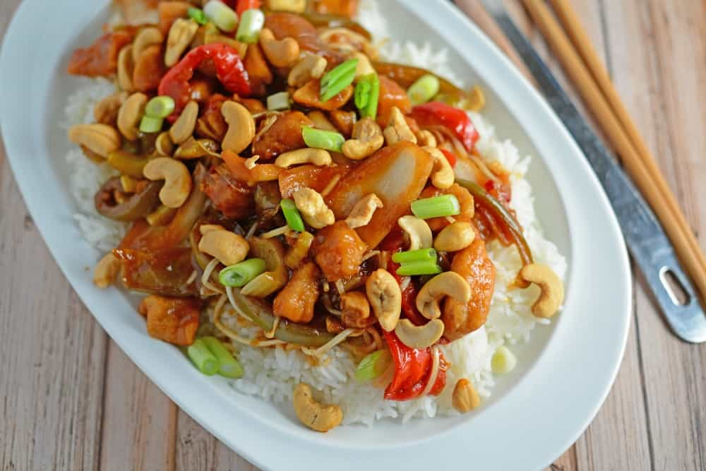 Cashew chicken over rice on a white plate