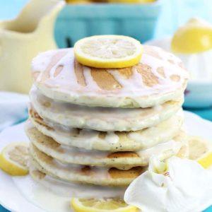 Stack of lemon poppyseed pancakes with white glaze and lemons