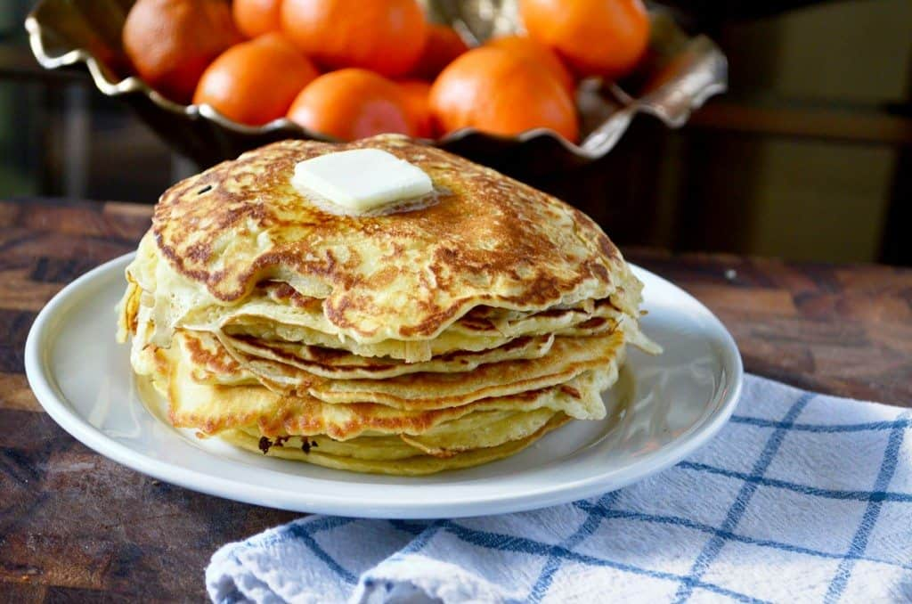 Stack of thin pancakes with a bowl of oranges