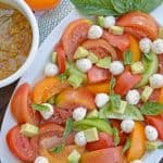 Tomato Salad with Mustard Bacon Dressing is the ultimate summer side dish using lush tomatoes, avocado mozzarella basil. Make it ahead for any party or BBQ. #tomatosalad #tomatorecipes www.savoryexperiments.com