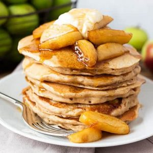 Apple pie pancakes on a white plate topped with apples