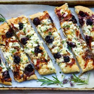 Balsamic cherry feta pizza cut into slices on a tray